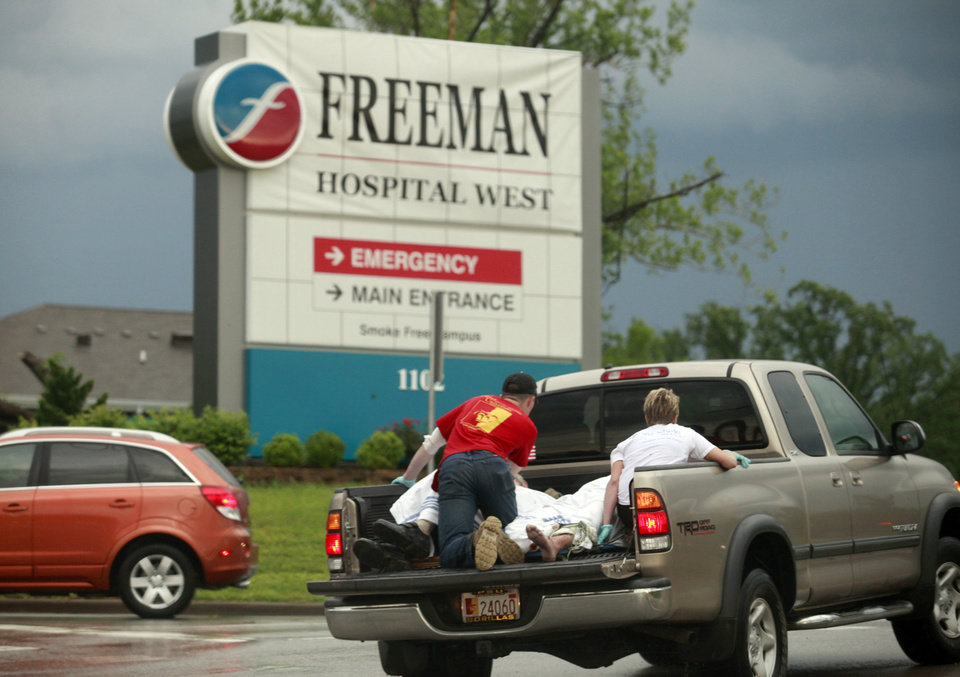 Photo - A pickup truck with what looked like two rescue workers and two injured people weaves in and out of traffic to get to Freeman Hospital West in Joplin, Mo. after the town was hit by a tornado on Sunday, May 22, 2011. (AP Photo/The Wichita Eagle, Jaime Green) ORG XMIT: KSWIE102