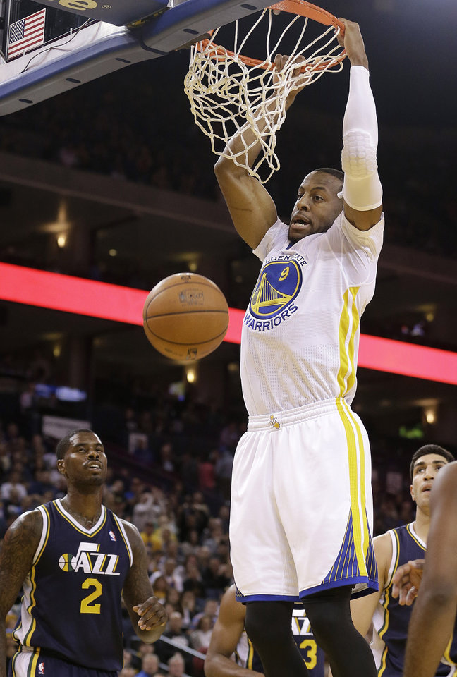 Photo - Golden State Warriors small forward Andre Iguodala (9) dunks over Utah Jazz power forward Marvin Williams (2) and others during the second quarter of an NBA basketball game in Oakland, Calif., Saturday, Nov. 16, 2013. (AP Photo/Jeff Chiu)