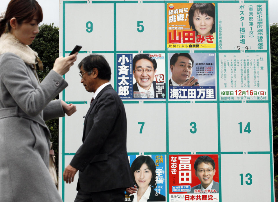 People walk by candidates\' poster boards for parliamentary elections in Tokyo Tuesday, Dec. 4, 2012. Leaders for Japan\'s biggest political parties kicked off Tuesday the campaign for parliamentary elections to be held in less than two weeks with visits to nuclear crisis-hit Fukushima prefecture. (AP Photo/Koji Sasahara)
