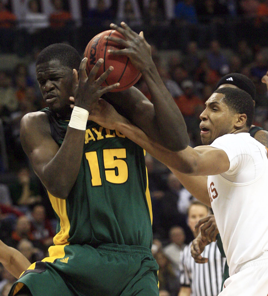 Photo - BIG 12 TOURNAMENT / COLLEGE BASKETBALL: Baylor's Mamadou Diene (15) controls a rebound as Texas' Gary Johnson (1) tries to get a hand on it in the second half during an NCAA college basketball game at the Big 12 Conference men's tournament in Oklahoma City, Friday, March 13, 2009.  (AP Photo/Sue Ogrocki) ORG XMIT: OKRH109