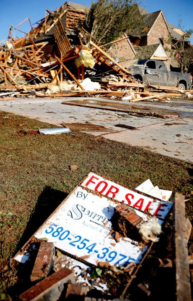 Photo -  A for sale sign sits in front of the a severely damaged home, Sunday, April 15, 2011. A tornado struck Woodward early Sunday morning. Photo by Sarah Phipps, The Oklahoman.