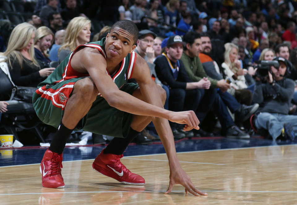 Photo - Milwaukee Bucks forward Giannis Antetokounmpo, of Greece, reacts after hurting his leg against the Denver Nuggets late in the fourth quarter of the Nuggets' 110-100 victory in an NBA basketball game in Denver on Wednesday, Feb. 5, 2014. (AP Photo/David Zalubowski)