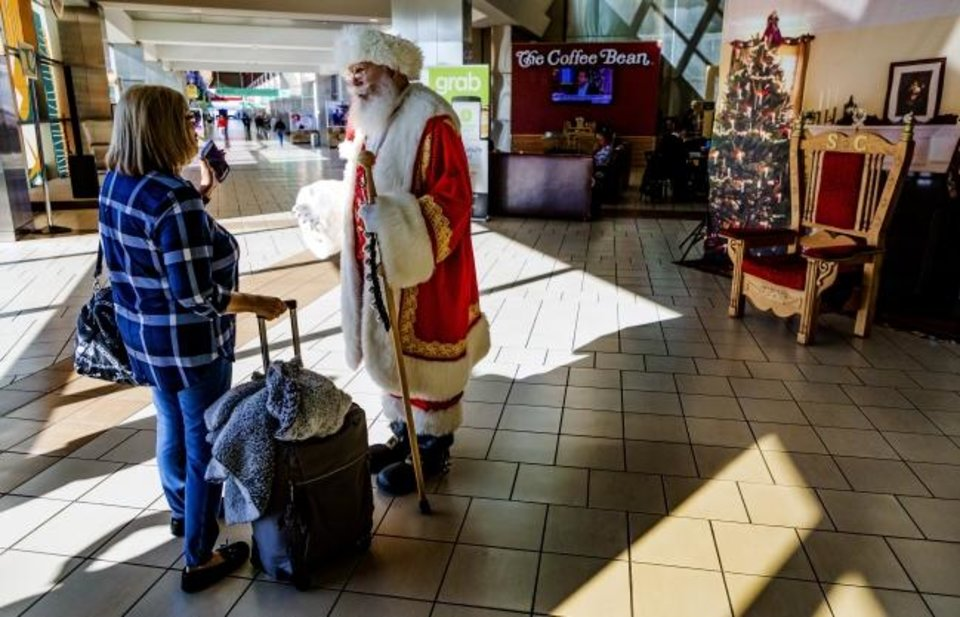 Photo -  Santa Claus visits with a traveler Thursday at Will Rogers World Airport in Oklahoma City. [Chris Landsberger/The Oklahoman]
