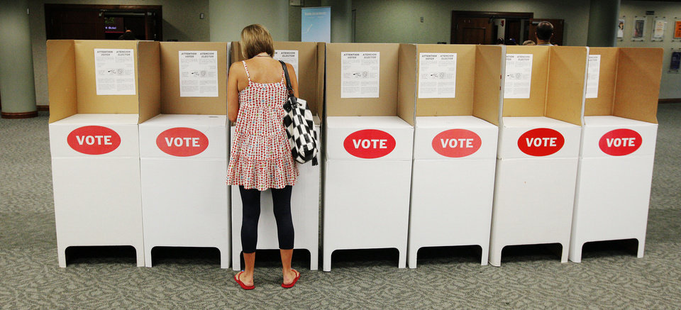 Photo - A lone voter in a voting booth marking her ballot at precinct 111 in Oklahoma City Tuesday, June 26, 2012.   Photo by Paul B. Southerland, The Oklahoman