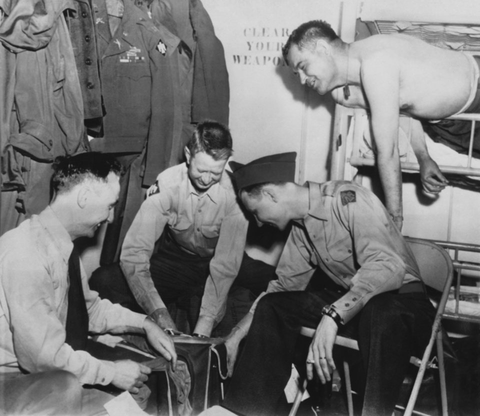 Photo - Home's Ahead for These Happy Thunderbird Officers.  As the transport Sylvester Antolak neared Seattle Sunday afternoon these Thunderbird officers had a pleasant job--packing their gear for landing.  They are (left to right):  Capt. Alfred M. Parsons, Shawnee; Capt. Eugene J. Roberts, Holdenville; Lieut. Norman C. Bowen, Ada and W/O Ooney E. Kennedy, Tulsa.  Associated Press Wirephoto.  Photographer and original date unknown.  Published in The Daily Oklahoma 04/14/1952 [LS].