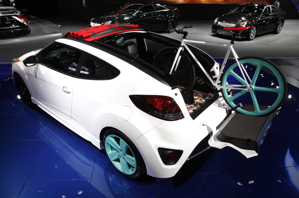 Photo - A bicycle is shown perched out the rear and rooftop of a Veloster coupe.at the North American International Auto Show in Detroit, Wednesday, Jan. 16, 2013. Transportation of the two-wheeled variety is sharing the floor at the auto show in Detroit along with the latest cars, trucks and concept vehicles. Bikes weren't the focus of presentations during this week's press previews, but they're often used in marketing cars. (AP Photo/Paul Sancya)