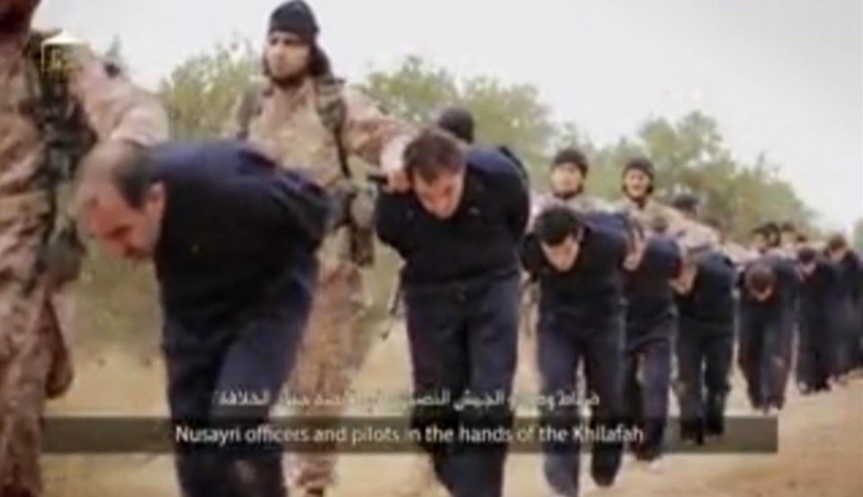 Photo - This still image taken from an undated video published on the Internet by the Islamic State group militants and made available, Sunday, Nov. 16, 2014, purports to show extremists marching Syrian soldiers before beheading them. The high-definition video later shows the beheadings of about a dozen men identified as Syrian military officers and pilots, all dressed in blue jumpsuits. The Associated Press could not independently verify the footage, though it appeared on websites used in the past by the Islamic State group, which now controls a third of Syria and Iraq. (AP Photo)