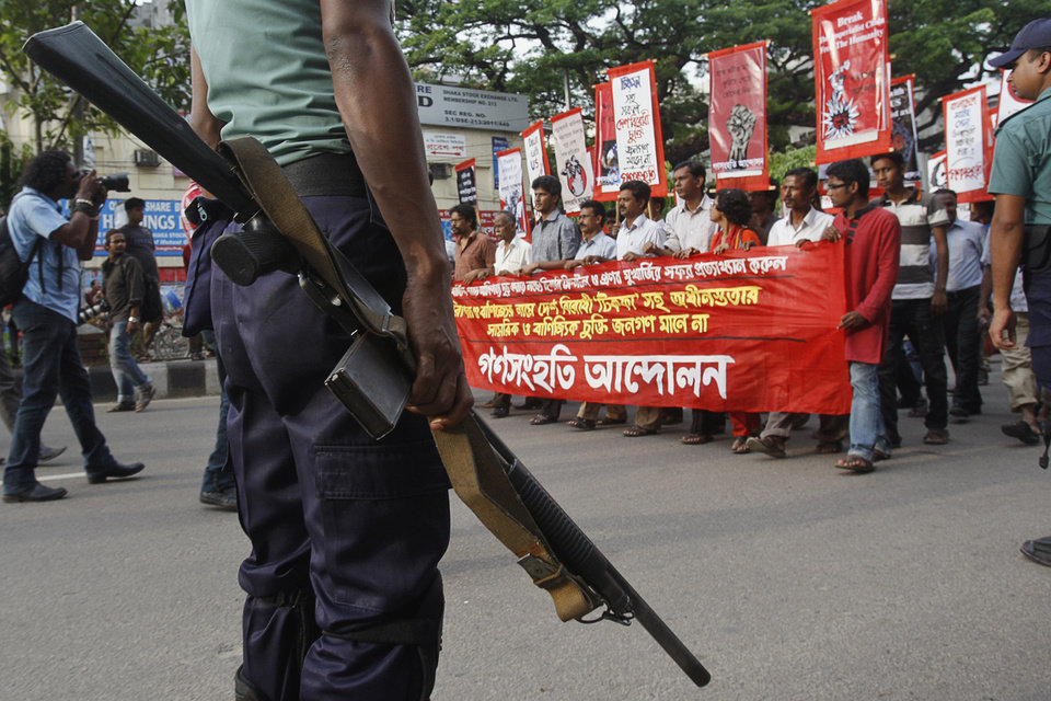 A police officer stands guard as protestors march in a rally against the visit of U.S. Secretary of State Hillary Clinton in Dhaka, Bangladesh, Friday, May 4, 2012. Clinton arrives Saturday for an official visit to the country. Banner reads 'Go back Hillary, we condemn her visit'.� (AP Photo/Pavel Rahman)