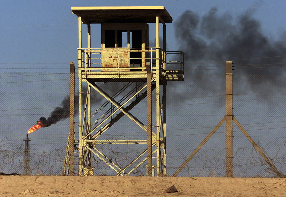 Photo - File - In this Monday, Oct. 6, 2003 file photo, an abandoned watchtower and lines of barbed wire are seen surrounding Iraq's largest oil refinery as smoke rises from a petroleum gas flare, in the city of Beiji, north of Baghdad. On Wednesday, June 18, 2014, a top Iraqi security official said Islamic militants of the al-Qaida-inspired Islamic State of Iraq and the Levant laid siege to Iraq's largest oil refinery late Tuesday night, threatening a facility key to the country's domestic supplies as part of their ongoing lightning offensive across the country. The Beiji refinery accounts for a little more than a quarter of the country's entire refining capacity and any lengthy outage at Beiji risks long lines at the gas pump and electricity shortages, adding to the chaos already facing Iraq. (AP Photo/Ivan Sekretarev, File)