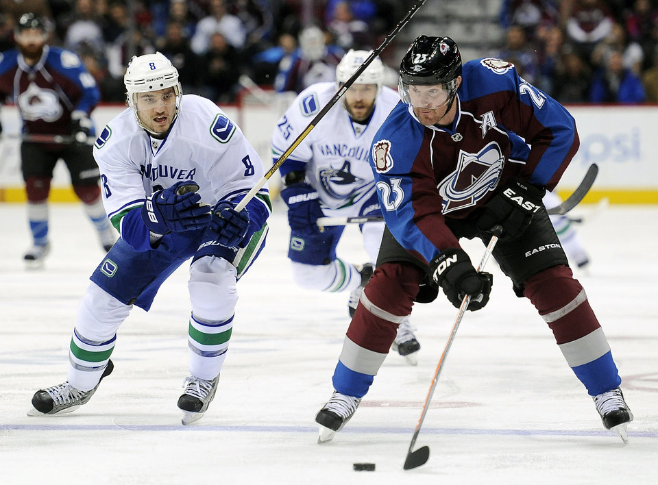 Photo - FILE - In this March 24, 2013, file photo, Vancouver Canucks defenseman Chris Tanev, left, defends Colorado Avalanche right wing Milan Hejduk, right, of Czech Republic, in an NHL hockey game in Denver. Hejduk, 38, is retiring from the NHL after 14 seasons, all with the Avalanche. (AP Photo/Chris Schneider, File)