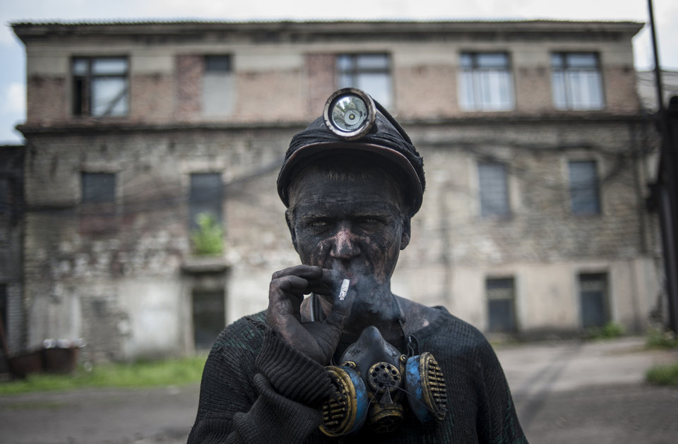 Photo - AP10ThingsToSee - A Ukrainian miner smokes at the Kalinin mine in eastern Ukraine city of Horlivka, Wednesday, May 14, 2014. The Ukrainian government agreed to launch talks on decentralizing power Wednesday as part of a European-backed peace plan. (AP Photo/Evgeniy Maloletka)