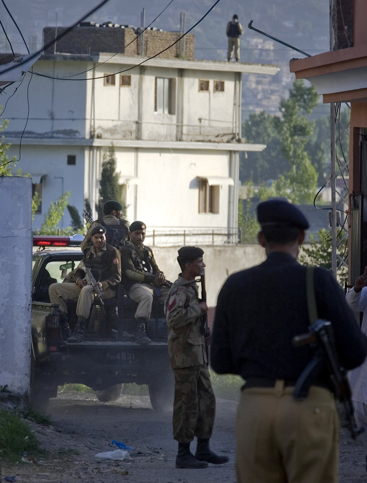 Photo - Pakistan army soldiers and a police officer patrol past the house, background, where it is believed al-Qaida leader Osama bin Laden lived in Abbottabad, Pakistan on Monday, May 2, 2011. Bin Laden, the mastermind behind the Sept. 11, 2001, terror attacks that killed thousands of people, was slain in his hideout in Pakistan early Monday in a firefight with U.S. forces, ending a manhunt that spanned a frustrating decade. (AP Photo/Anjum Naveed) ORG XMIT: ANJ114