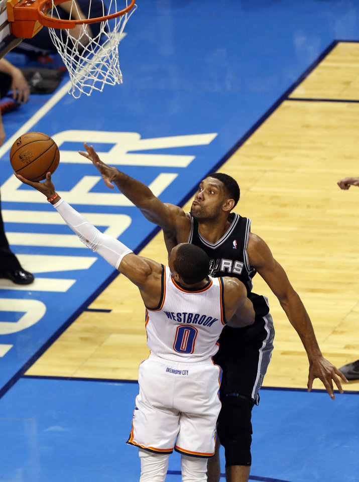 Photo - Oklahoma City's Russell Westbrook (0) goes up for a basket as San Antonio's Tim Duncan (21) defends during Game 3 of the Western Conference Finals in the NBA playoffs between the Oklahoma City Thunder and the San Antonio Spurs at Chesapeake Energy Arena in Oklahoma City, Sunday, May 25, 2014. Photo by Nate Billings, The Oklahoman