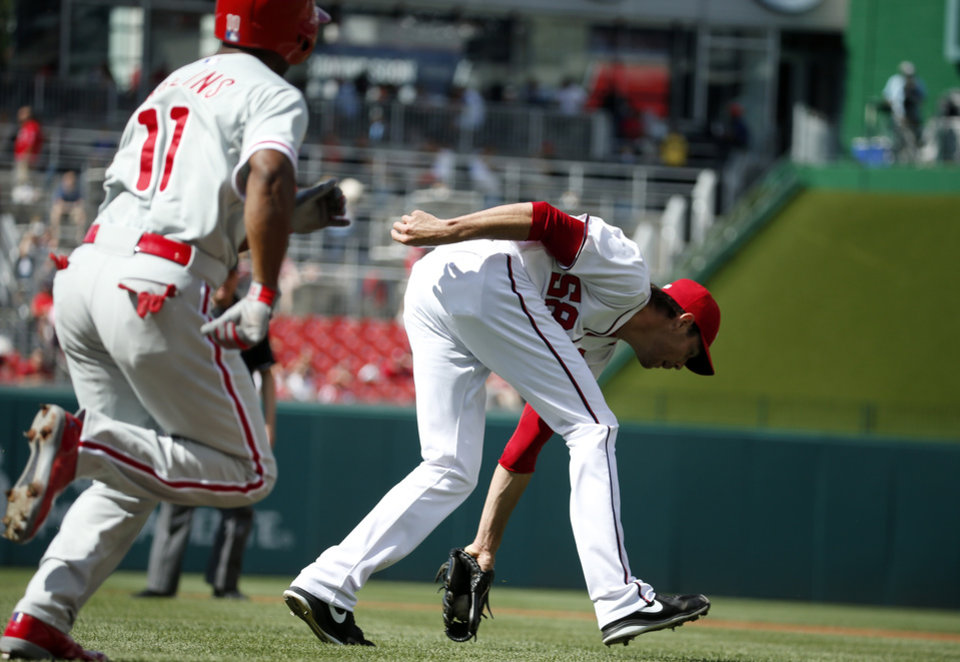 Washington Nationals starting pitcher Doug Fister (58) fields the sacrifice bunt by Philadelphia Phillies\' Jimmy Rollins (11), who was out at first base on the play, during the first inning of a baseball game at Nationals Park Thursday, June 5, 2014, in Washington. (AP Photo/Alex Brandon)