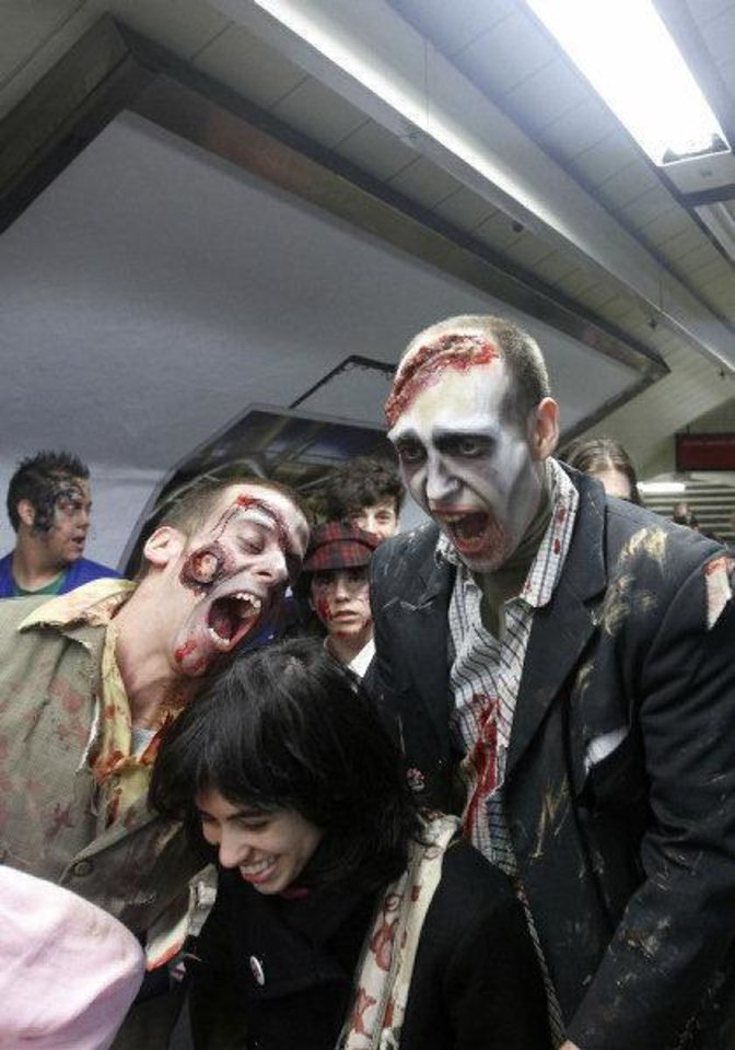 Photo - People dressed and made up as Zombies try to scare a passenger on the platform of a metro train station during the annual Zombie march in Madrid, Saturday Feb. 27, 2010. The zombie march is in homage by fans to the Zombie film genre and to U.S. director George A. Romero, famous for his Zombie horror movies. (AP Photo/Paul White)