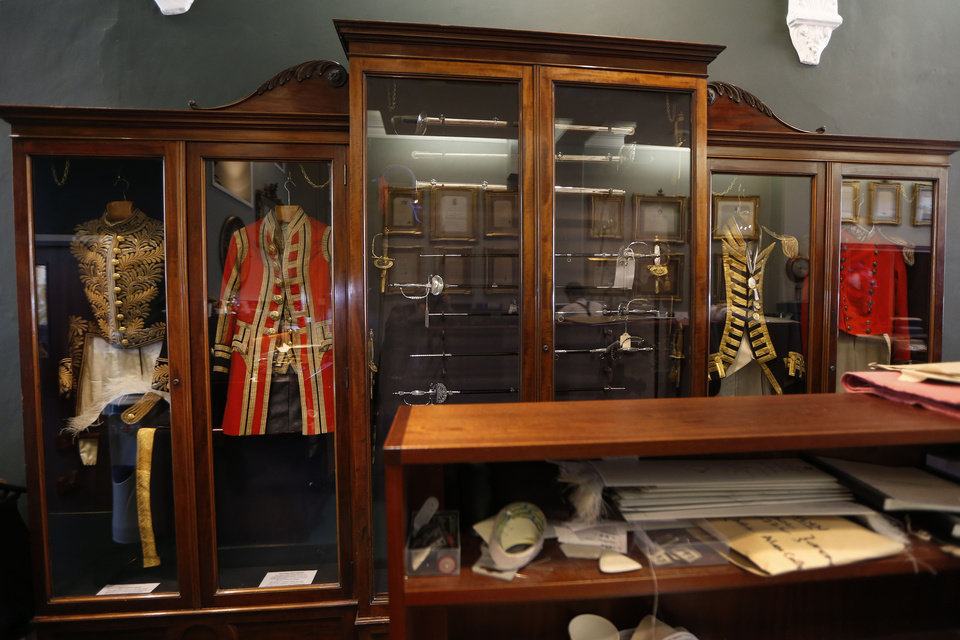 Photo - In this photo taken Friday, June 6, 2014,  A collection of uniforms, including a 1905 Privy Council uniform, left, and a 1875 Royal Household Semi State Livery uniform, second left, are on display in Henry Poole & Co tailor, the first shop to set up in Savile Row in 1846, in London. In the world of women's fashion, London often seems to play second fiddle to other style capitals: It lacks the allure of Paris's haute couture, or the polish of Milan's luxury labels. But it's a whole different story when it comes to dressing men. Steeped in a rich history of tailoring for kings, army generals and the world's wealthiest men, London is now marketed as the home of men's fashion - the original birthplace of the tuxedo jacket, the bowler hat and the three-piece suit, among other classic items. When trendy designers like Alexander McQueen and Burberry kick off the new season's menswear shows in the British capital Sunday, the catwalks will be staged just blocks away from elite tailoring houses that have been perfecting their craft for over a century. Savile Row, a street lined with more than a dozen tailors and a living museum of the English love affair with luxury menswear, has a long-standing tradition closely tied to a history in royal dress, military uniforms and gentry sports like horseback riding and hunting. (AP Photo/Sang Tan)