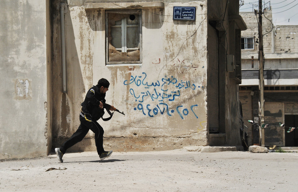Photo -   A Syrian rebel runs for cover at the Sunni district of Jabb al-Jandali in Homs, Syria, Monday, May 14, 2012. Syrian troops shelled the rebel-held town, sparking intense clashes that sent bloodied victims flooding into hospitals and clinics, activists said. The violence around the country is eroding an internationally brokered peace plan that many observers see as the last hope to calm the 14-month-old crisis. Arabic writing on the wall is an advertisement. (AP Photo/Fadi Zaidan)
