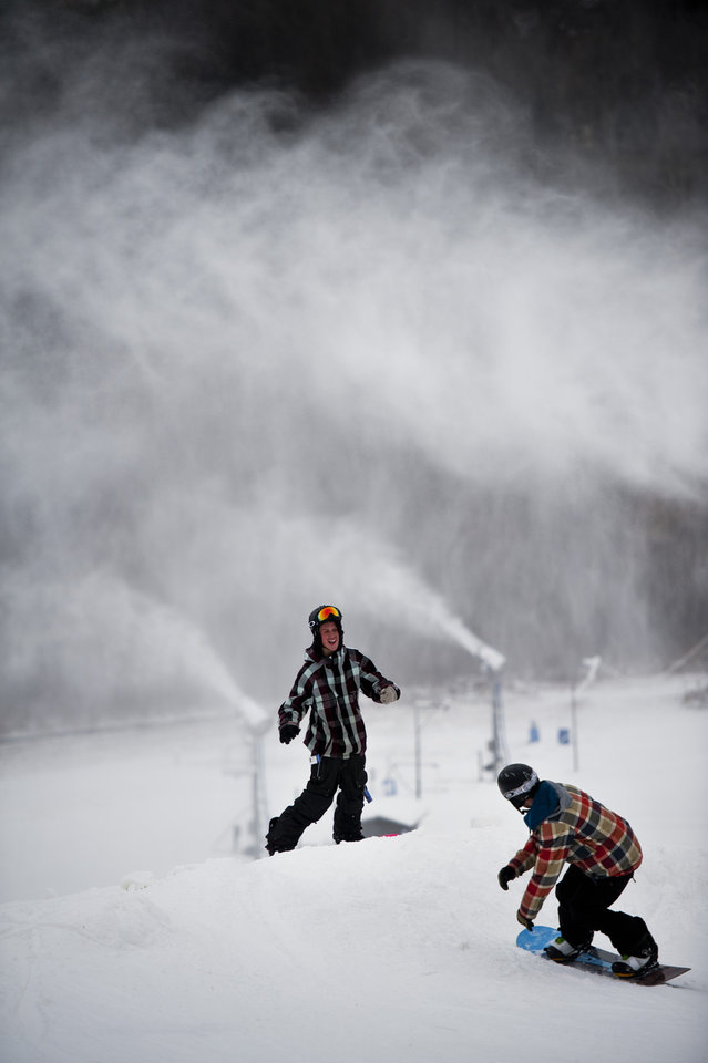 Photo - Snowboarders gather near the edge of a drop on Quad hill during Cannonsburg Ski Hill's opening day on Wednesday, Dec. 26, 2012 in Belmont, Mich. (AP Photo/The Grand Rapids Press, Matthew Busch)