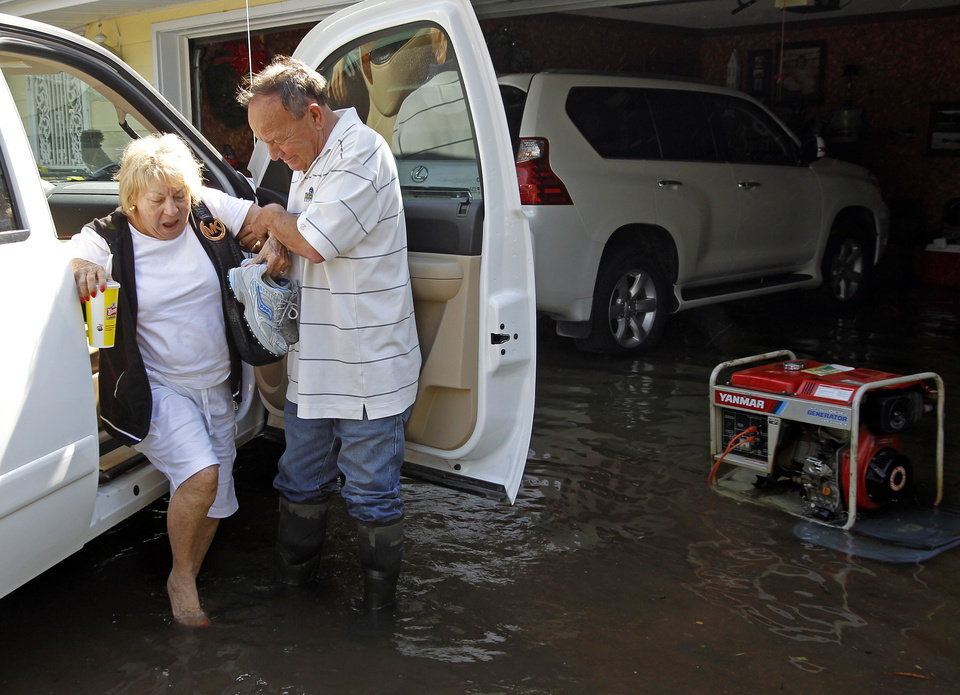 Photo - Max Herron helps his wife, LaJuan, out of a truck at their flooded home on Wednesday, April 27, 2011, in West Memphis, Ark. Strong storms hit the South Wednesday for the second straight day. (AP Photo/Mark Humphrey)