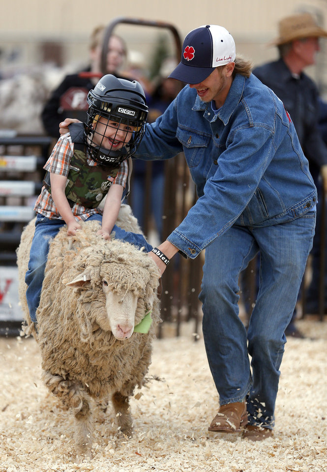 Jasper Ramirez, 3, of Oklahoma City tries mutton busting as Matt Phillips hold on to him the National Circuit Finals Rodeo at the State Fair Arena in Oklahoma City, Friday, April 5, 2013. Photo by Sarah Phipps, The Oklahoman