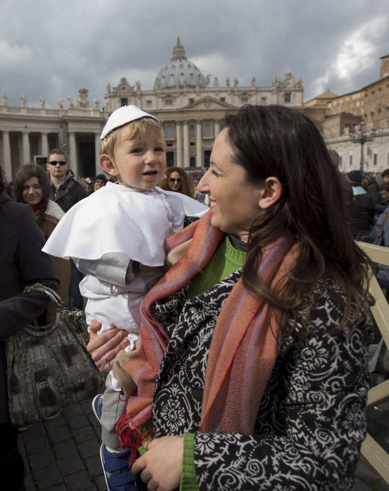 Photo - Paola Ciabattini smiles to her 19-month-old son Daniele De Sanctis, dressed up as a pope, during Pope Francis' weekly general audience in St. Peter's Square at the Vatican, Wednesday, Feb. 26, 2014. Francis kissed the child as the new must-have Carnival costume made its debut at the pope's general audience Wednesday. Daniele, who was crying, was hoisted up to Francis as he drove by in his open-topped jeep. During Carnival in Italy, children often go to school and spend their weekends dressed up in pirate, princess — and now pope — costumes. Carnival, also known as mardi gras, marks the period before the church's solemn Lenten season begins. Ciabattini said she dressed her son as a pope in a demonstration of affection towards Pope Francis. (AP Photo/Alessandra Tarantino)
