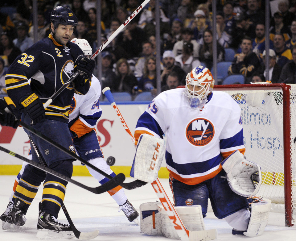 Buffalo Sabres\' John Scott (32) battles for a rebound after a save from New York Islanders\' Anders Nilsson (45), of Sweden, during the first period of an NHL hockey game in Buffalo, N.Y., Sunday April 13, 2014. (AP Photo/Gary Wiepert)