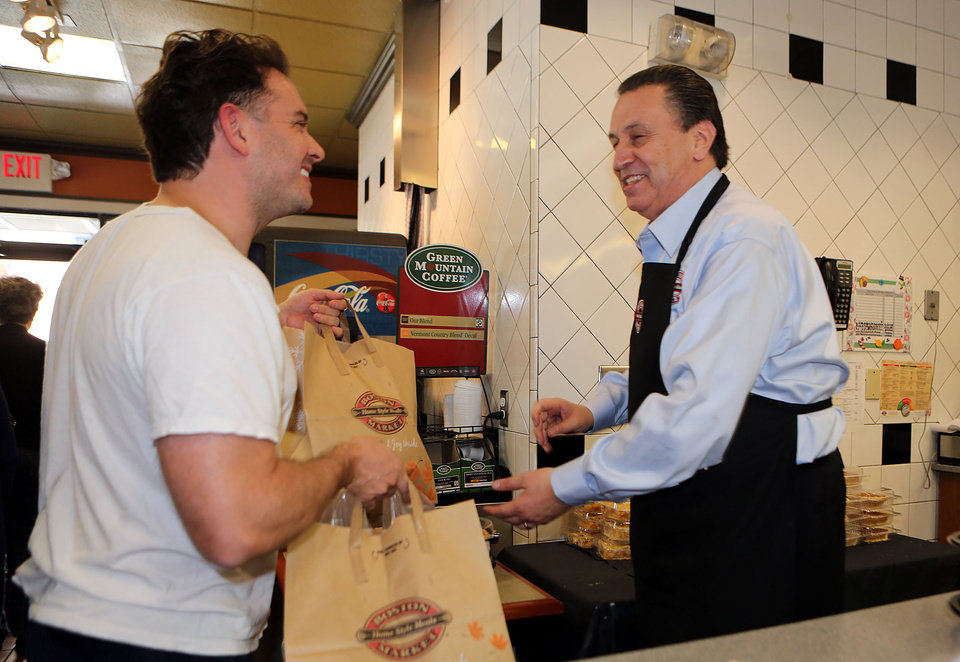 Photo - This Nov. 22, 2012 photo provided by Boston Market shows Boston Market CEO George Michel, right, working inside a company's Miami-area restaurant on the home style restaurant chains busiest day of the year, Thanksgiving, in Miami. Boston Market Corp. is reporting record Thanksgiving sales this year, and it's already planning for next Thanksgiving. The Golden, Colo.-based restaurant chain had not yet released specific dollar figures but said total sales per restaurant from Nov. 19 to Nov. 23 were up 13 percent from a comparable period last year. (AP Photo/Boston Market, Marc Serota)