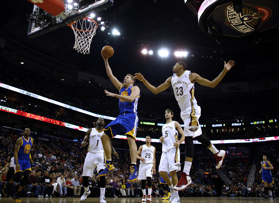 Photo - Golden State Warriors power forward David Lee, front left, drives to the basket past New Orleans Pelicans power forward Anthony Davis (23), point guard Tyreke Evans (1) and center Jeff Withey (5)during the first half of an NBA basketball game in New Orleans, Saturday, Jan. 18, 2014. (AP Photo/Jonathan Bachman)