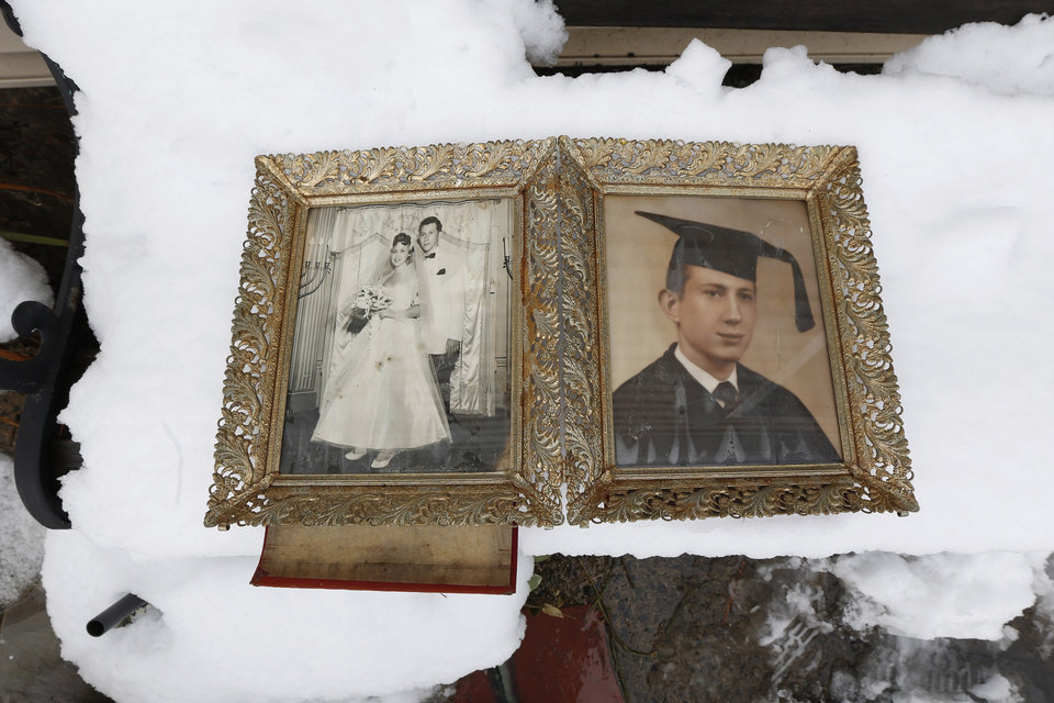 Photo - Photographs of Elliott Miller's wedding day and graduation lay on a snow covered bench as Jeanene Miller tries to dry out the pictures of her in-laws which were damaged during floods caused by Superstorm Sandy, Thursday, Nov. 8, 2012, in Point Pleasant, N.J.  The New York-New Jersey region woke up to wet snow and more power outages Thursday after the nor'easter pushed back efforts to recover from Superstorm Sandy, that left millions powerless and dozens dead last week. (AP Photo/Julio Cortez)  ORG XMIT: NJJC120