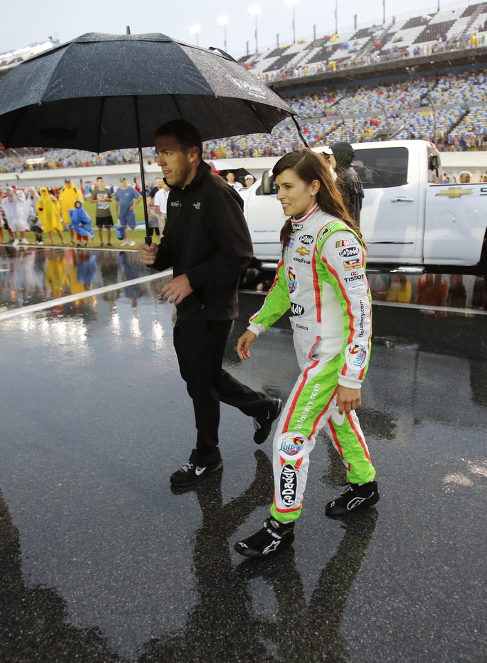 Photo - Danica Patrick, right, walks back to her garage after driver introductions during a rain delay before the NASCAR Sprint Cup series auto race at Daytona International Speedway in Daytona Beach, Fla., Saturday, July 5, 2014. (AP Photo/Terry Renna)
