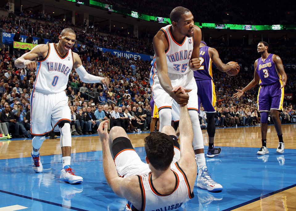 Oklahoma City\'s Kevin Durant (35) helps Nick Collison (4) up after he took a charge from Los Angeles\' Devin Ebanks (3) as Oklahoma City\'s Russell Westbrook (0) reacts during an NBA basketball game between the Oklahoma City Thunder and the Los Angeles Lakers at Chesapeake Energy Arena in Oklahoma City, Friday, Dec. 7, 2012. Oklahoma City won, 114-108. Photo by Nate Billings, The Oklahoman