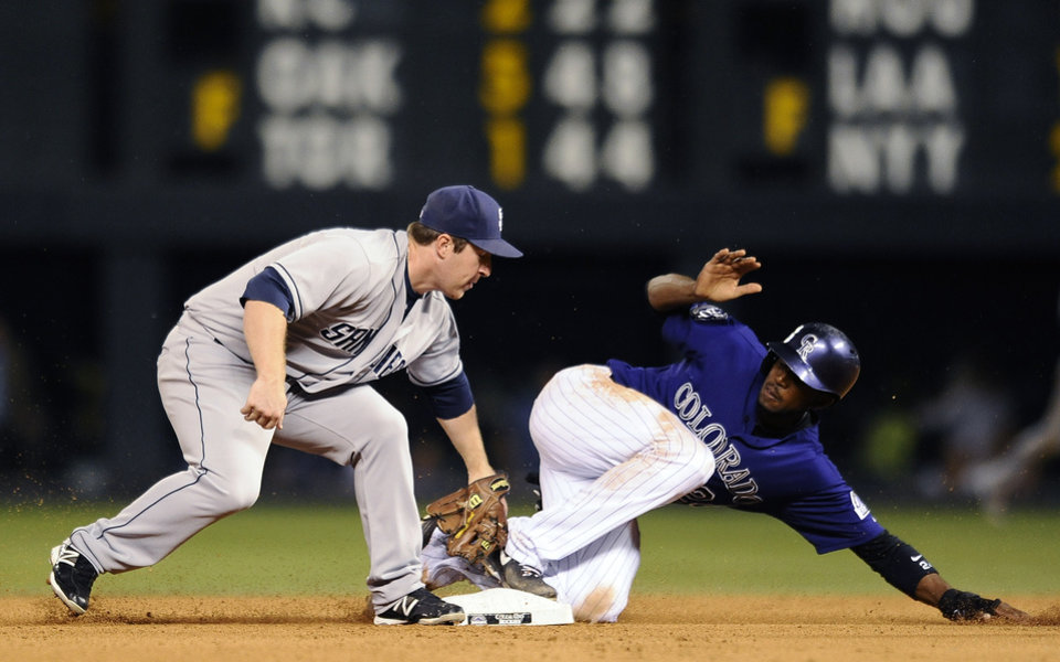 Photo - Colorado Rockies Dexter Fowler, right, slides safely into second base under the tag by San Diego Padres second baseman Jedd Gyorko in the 4th inning of a baseball game on Monday, Aug. 12, 2013 in Denver. (AP Photo/Chris Schneider)