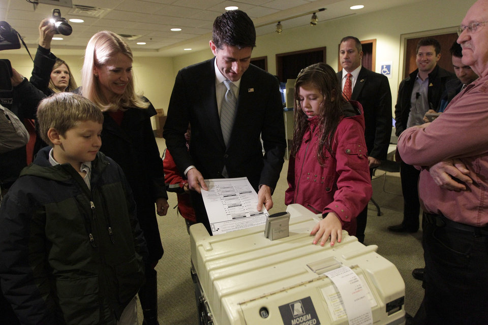 Photo -   Republican vice presidential candidate, Rep. Paul Ryan, R-Wis., casts his ballot as his wife Janna, son Charlie, left and daughter Liza watch, Tuesday, Nov. 6, 2012 at the Hedberg Public Library in Janesville, Wis. (AP Photo/Mary Altaffer)