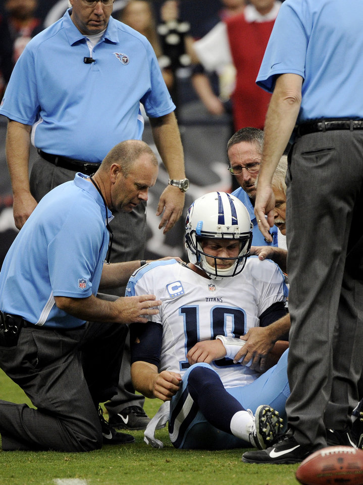 Photo -   Tennessee Titans quarterback Jake Locker (10) is helped off the field after being sacked by Houston Texans strong safety Glover Quin in the first quarter of an NFL football game Sunday, Sept. 30, 2012, in Houston. (AP Photo/Dave Einsel)