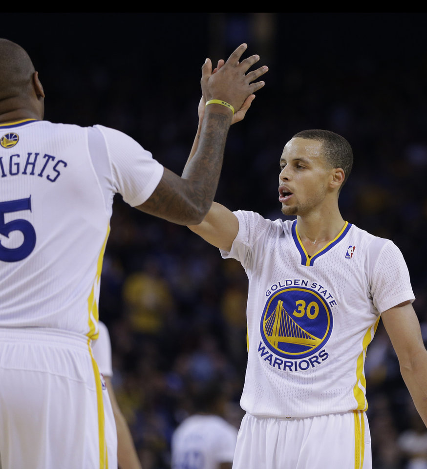 Photo - Golden State Warriors' Stephen Curry, right, is congratulated by Marreese Speights after Curry scored against the Los Angeles Lakers during the second half of an NBA basketball game, Saturday, Dec. 21, 2013, in Oakland, Calif. (AP Photo/Ben Margot)