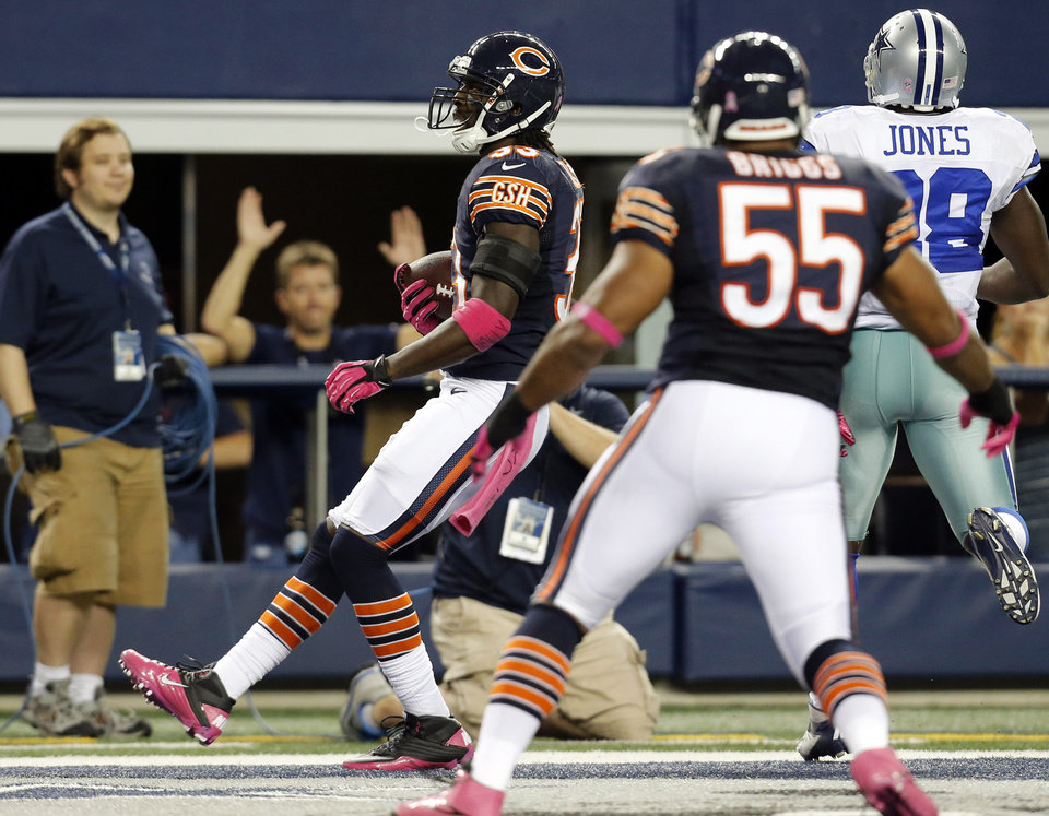 Photo -   Chicago Bears cornerback Charles Tillman returns an interception for a touchdown past Dallas Cowboys running back Felix Jones (28) as Bears' Lance Briggs (55) watches during the first half of an NFL football game, Monday, Oct. 1, 2012, in Arlington, Texas. (AP Photo/Sharon Ellman)
