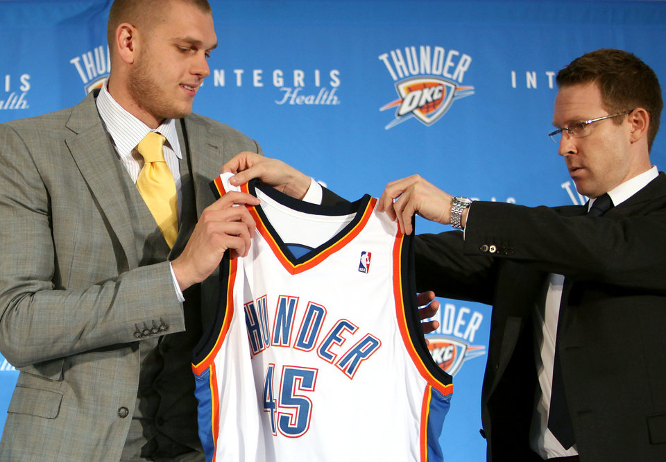 Photo - Sam Presti (right) holds out an Oklahoma City Thunder jersey for Cole Aldrich during a press conference at the Thunder Practice facility in Oklahoma City on Monday, July 12, 2010. Photo by John Clanton, The Oklahoman ORG XMIT: KOD