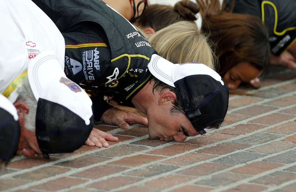 Photo - Jeff Gordon celebrates by kissing the bricks after winning the NASCAR Brickyard 400 auto race at Indianapolis Motor Speedway in Indianapolis, Sunday, July 27, 2014.  (AP Photo/Robert Baker)