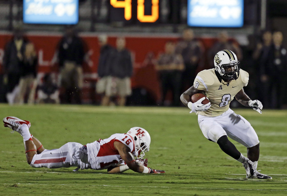 Photo - Central Florida running back Storm Johnson (8) gains yardage as he gets past Houston's Adrian McDonald (16) during the first half of an NCAA college football game in Orlando, Fla., Saturday, Nov. 9, 2013. (AP Photo/John Raoux)