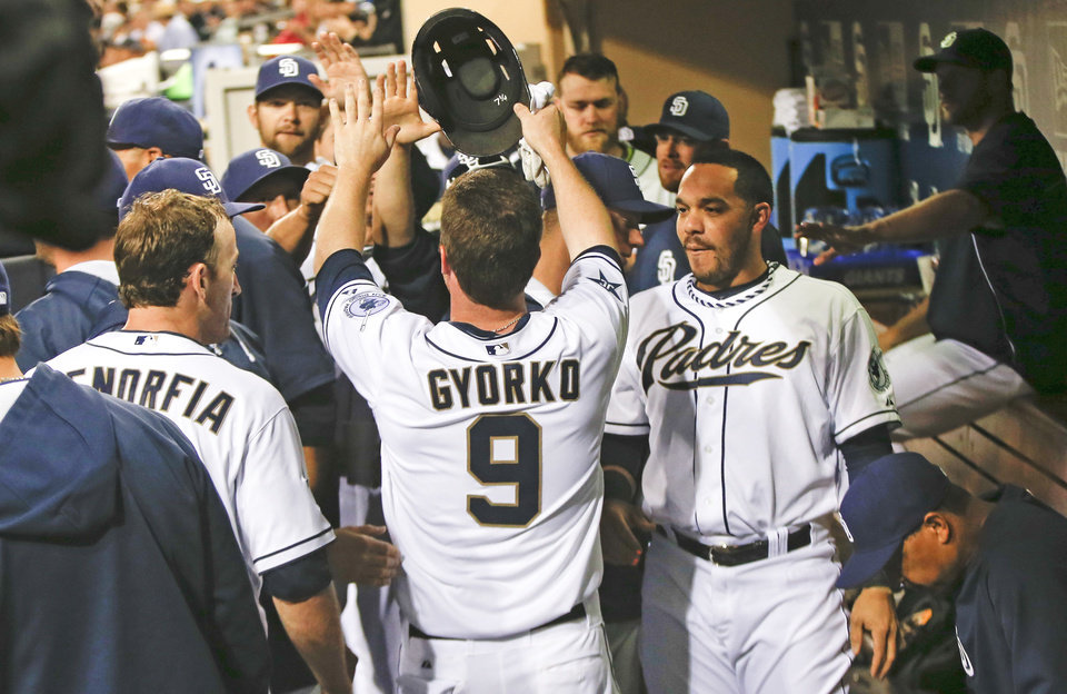 Photo - San Diego Padres' Jedd Gyorko is congratulated by teammates after scoring and driving in a run against the Detroit Tigers during the first inning of a baseball game Friday, April 11, 2014, in San Diego. (AP Photo/Lenny Ignelzi)