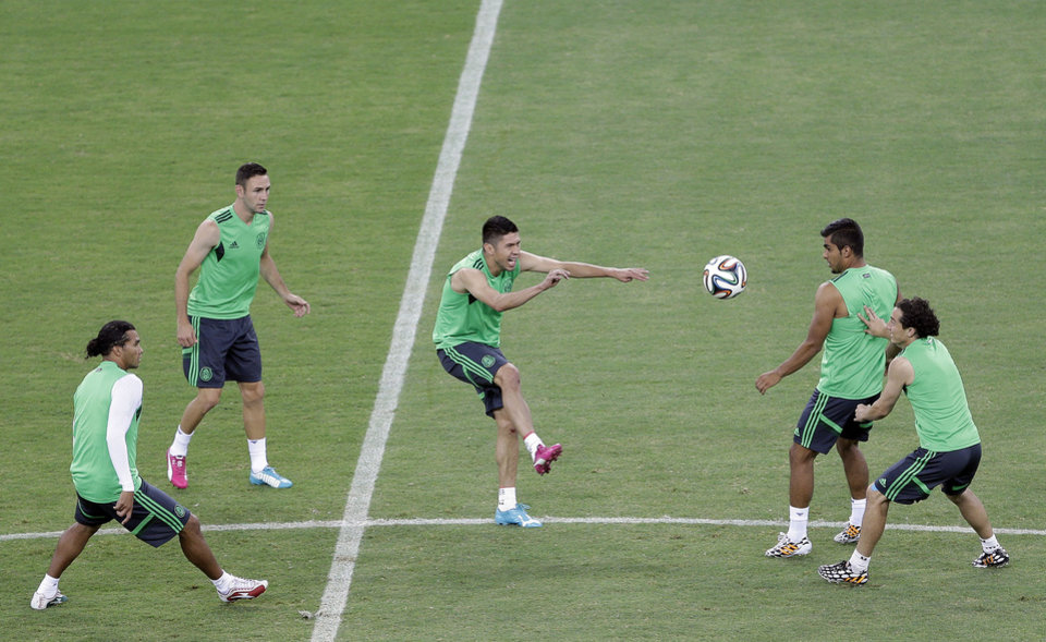 Photo - Mexico's Oribe Peralta, center, practices with teammates during an official training session the day before the group A World Cup soccer match between Brazil and Mexico, at the Arena Castelao in Fortaleza, Brazil, Monday, June 16, 2014.  (AP Photo/Andre Penner)