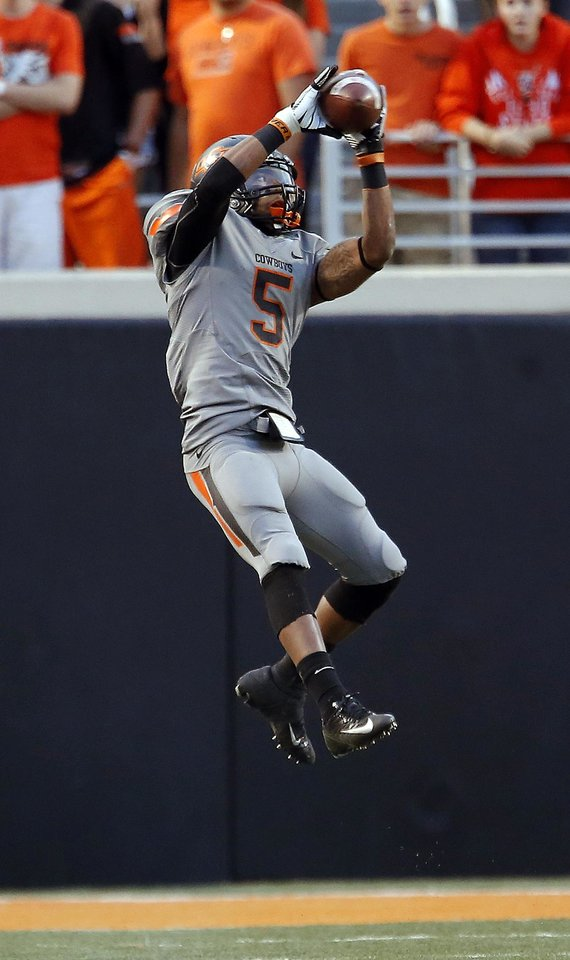 Photo - Oklahoma State's Josh Stewart (5) catches a pass in the third quarter during a college football game between Oklahoma State University (OSU) and the West Virginia University at Boone Pickens Stadium in Stillwater, Okla., Saturday, Nov. 10, 2012. Photo by Sarah Phipps, The Oklahoman