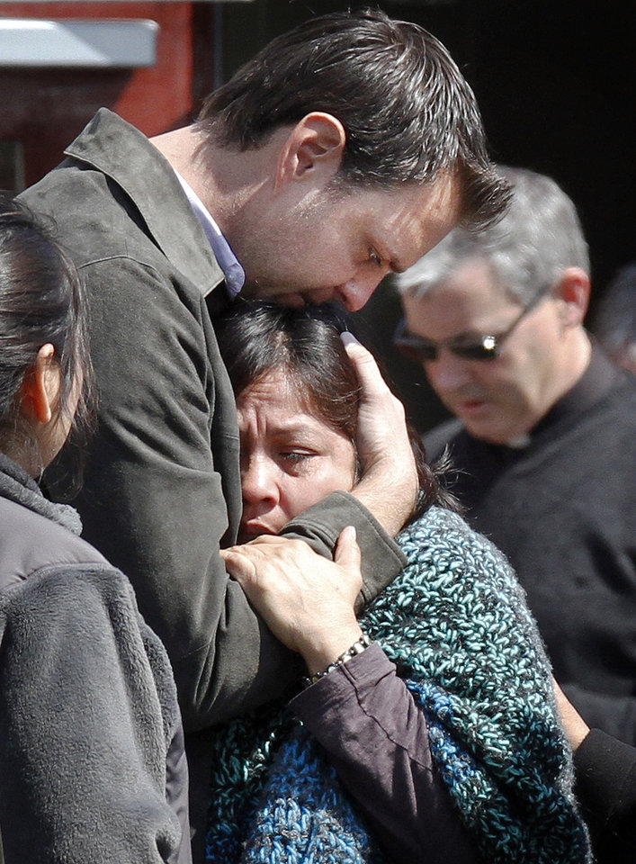 Photo -   Luzmila Garcia, center, is consoled after the body of her missing son, Boston College student Franco Garcia, was recovered at Chestnut Hill Reservoir in Boston, Wednesday, April 11, 2012. Franco Garcia disappeared Feb. 22 after leaving a popular bar near the college. (AP Photo/Michael Dwyer)