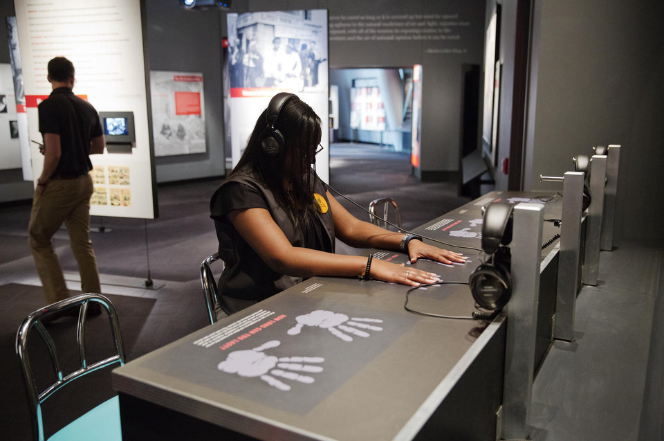 "Photo - In this June 16, 2014 photo, volunteer Monique Jenkins listens through headphones to increasingly intense taunts and threats endured by protesters during staged sit-ins at the ""whites only"" dining counters as part of an exhibit at the newly built National Center for Civil and Human Rights in Atlanta. The new museum about the history of civil rights opens next week in Atlanta, the city where Martin Luther King Jr. was based. But the National Center for Civil and Human Rights also explores other human rights struggles, from women's rights and LGBT issues to immigration and child labor. The museum devotes separate galleries to modern human rights issues and the U.S. civil rights movement of the 1950s and '60s, but also demonstrates how the two struggles are related. Visitors learn history through interactive exhibits and stories of real people. (AP Photo/David Goldman)"