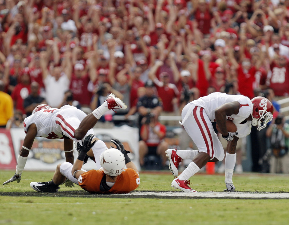 Photo - OU's Tony Jefferson (1) intercepts a pass intended for UT's Jaxon Shipley (8) near OU's Aaron Colvin as fans cheer in the first half during the Red River Rivalry college football game between the University of Oklahoma Sooners (OU) and the University of Texas Longhorns (UT) at the Cotton Bowl in Dallas, Friday, Oct. 7, 2011. Photo by Nate Billings, The Oklahoman