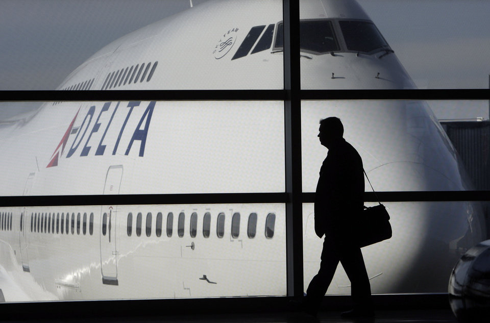 Photo - FILE - In this file photo made Jan. 21, 2010, a passenger walks past a Delta Airlines 747 aircraft in McNamara Terminal at Detroit Metropolitan Wayne County Airport in Romulus, Mich. Delta Air Lines on Tuesday, July 22, 2014 canceled all flights to Israel until further notice, citing reports that a rocket landed near Tel Aviv's Ben Gurion Airport. (AP Photo/Paul Sancya, File)