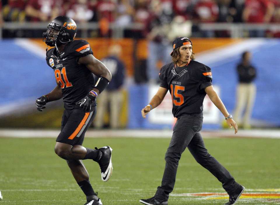 Photo - Rickie Fowler walks off the field with Oklahoma State's Justin Blackmon (81) before  the Fiesta Bowl between the Oklahoma State University Cowboys (OSU) and the Stanford Cardinal at the University of Phoenix Stadium in Glendale, Ariz., Monday, Jan. 2, 2012. Photo by Sarah Phipps, The Oklahoman
