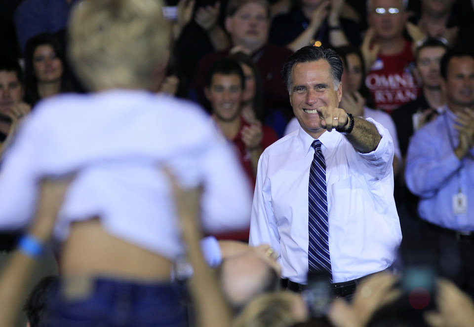 Photo -   Republican presidential candidate, former Massachusetts Gov. Mitt Romney points to a young boy being held up by a supporters during a campaign rally at Jet Machine, Thursday, Oct. 25, 2012, in Cincinnati. The company is a defense contractor. (AP Photo/Al Behrman)