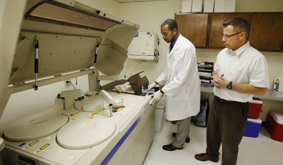 Photo - Lab technician Todd Britton loads drug testing specimens into an automated chemistry analyzer at CRG Laboratories as Jim Tedrow, laboratory director, looks on Wednesday in Oklahoma City.