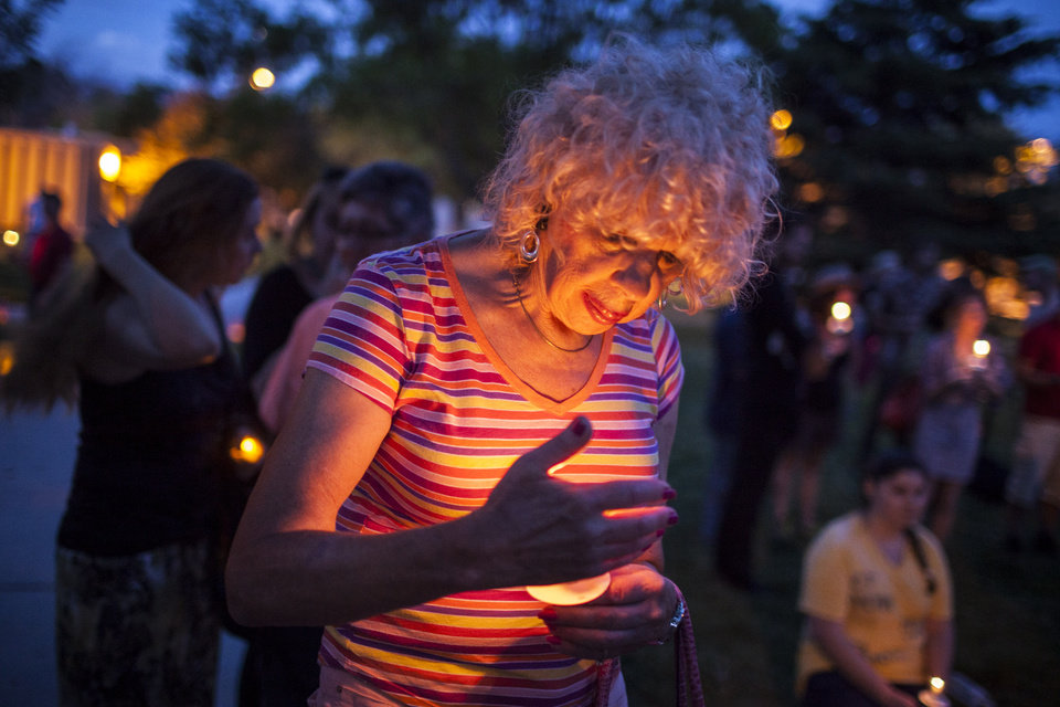 Photo - In this May 29, 2014 photo, Denee Mallon, center, participates in a candlelight vigil organized by Albuquerque Pride in Albuquerque, N.M. A U.S. Department of Health and Services review board ruled Friday, May 30, in favor of Mallon, a 74-year-old Army veteran, whose request to have Medicare pay for her genital reconstruction was denied two years ago. The decision recognizes sex reassignment surgeries as a medically necessary and effective treatment for individuals who do not identify with their biological sex. (AP Photo/Craig Fritz)